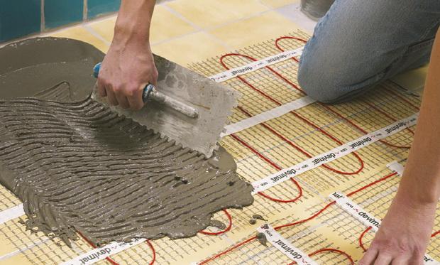 Укладка промежуточного слоя плиточного клея на нагревательный мат